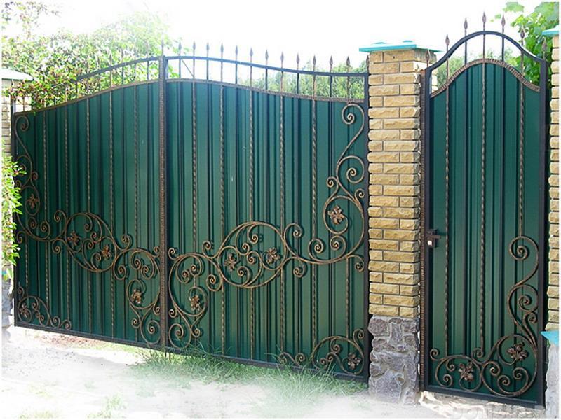 Декорированный забор из профнастила с кирпичными столбами и кованой решеткой