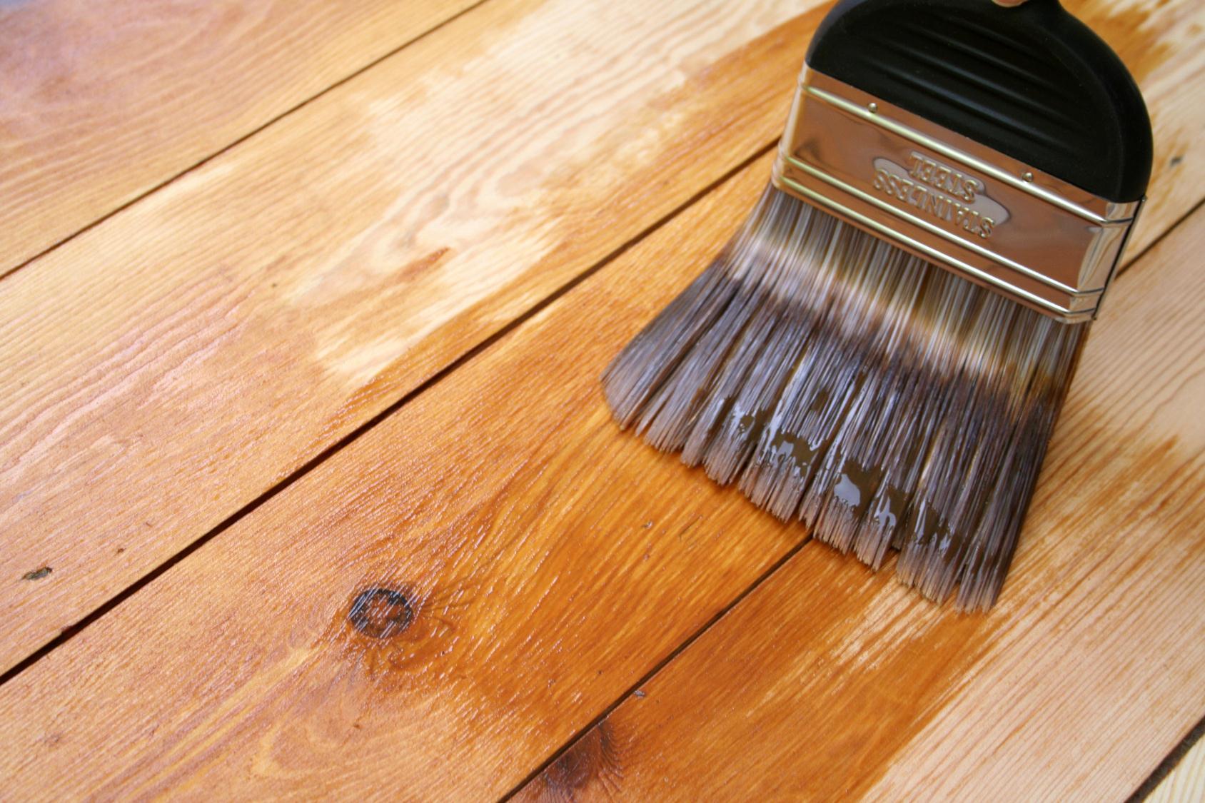 Нанесение лака для защиты деревянной поверхности пола беседки