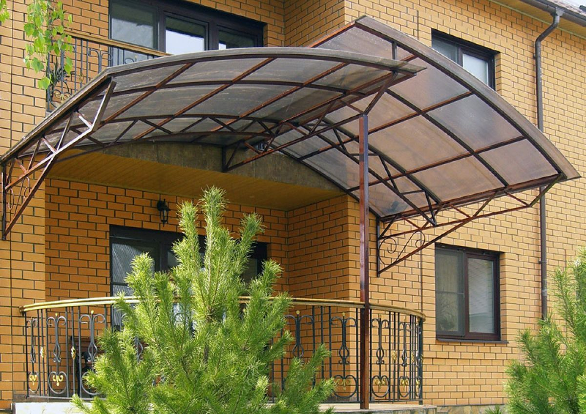 Оригинальный двухскатный навес из поликарбоната над крыльцом дачного домика