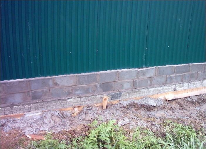 Чем закрыть щель под забором из профлиста до земли - кирпич