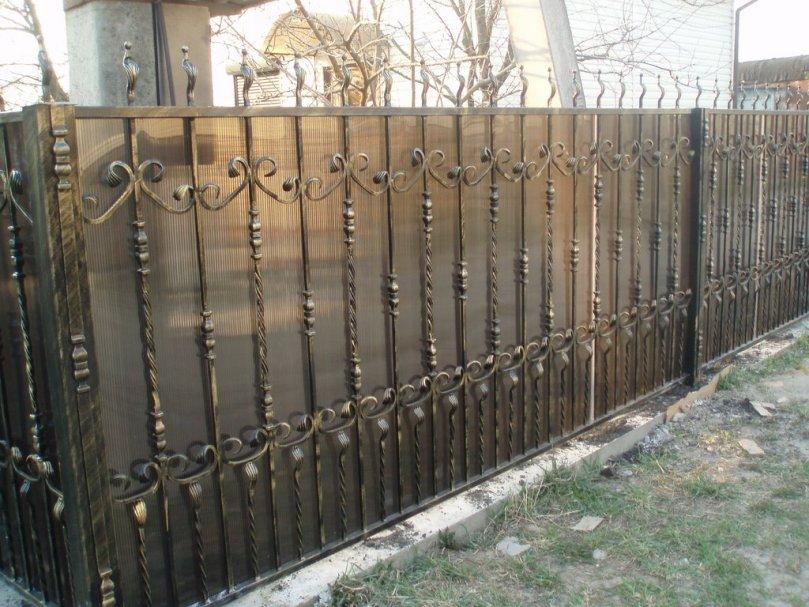 Кованый забор из поликарбоната на загородном участке