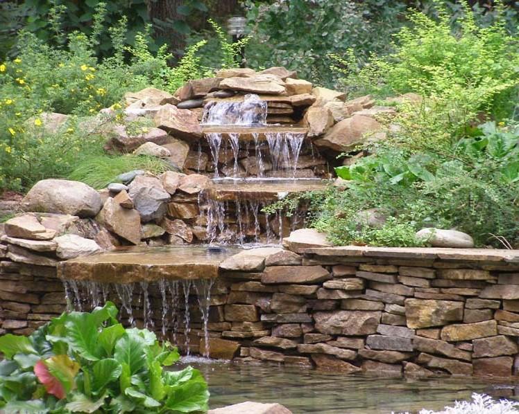 Альпийская горка с многоярусным водопадом в саду на даче