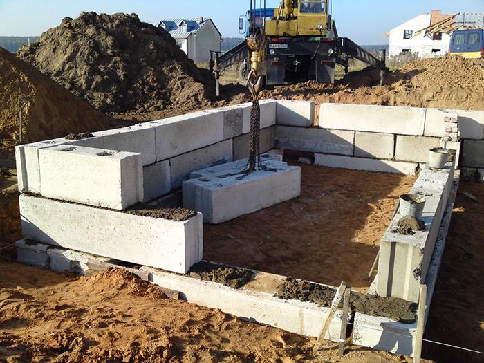 Установка блоков ФБС с помощью крана для постройки фундамента